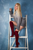 Young woman in red boots is sitting on the stairs. Beautiful girl in a gray cozy sweater. Lovely blonde with long legs on the stairs. young woman in red boots royalty free stock photos