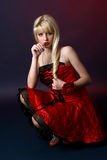 young woman in a red satiny dress Stock Photography