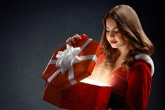 Sexy young woman in red suit of Santa Claus  with gifts. On a da Royalty Free Stock Image