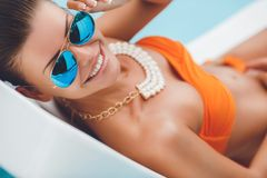 Sexy young woman relaxing on deck chair. Royalty Free Stock Photo