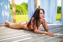 Sexy young woman lying relaxing on deck chair near pool Stock Photography