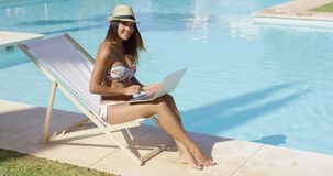 Sexy young woman relaxing at the swimming pool. Sitting in a deck chair in bikini and trendy hat working on a laptop stock video footage