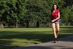 Sexy young woman roller skating in park sunshine Stock Images