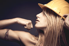 young woman with safety helmet showing muscles Stock Photography