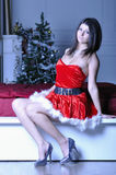 Sexy young woman in santa clause costume sit on bed Royalty Free Stock Image