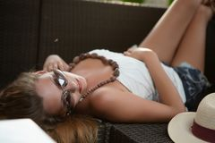 Sexy young woman. In glasses posing outdoors lying on the sofa dressed in tunic and shorts stock photo