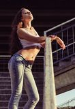 Sexy young woman in shirt and jeans stands on stairs at sunset time Royalty Free Stock Photo