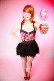 Sexy young woman showing candy. Redhair girl giving sweet lollipop Royalty Free Stock Photography