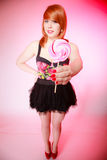 Sexy young woman showing candy. Redhair girl giving sweet lollipop Royalty Free Stock Photos