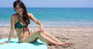 Sexy young woman sitting on a beach stock footage