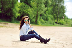 Sexy young woman sitting on a beach outdoor fashion portrait Royalty Free Stock Image