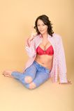 Sexy young woman sitting on floor in casual clothes revealing red bra Royalty Free Stock Photos