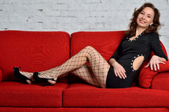 Sexy young woman sitting on a red couch. Stock Photos