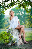 Sexy young woman sitting on stump in the forest Stock Photos