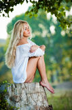 Sexy young woman sitting on stump in the forest Royalty Free Stock Photos