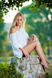 Sexy young woman sitting on stump in the forest Stock Photo