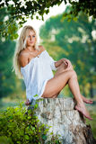 Sexy young woman sitting on stump in the forest Royalty Free Stock Photography