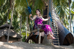 Sexy young woman sitting on the swing on the tropical beach, paradise island Bali, Indonesia. Sunny day, happy vacation Stock Photo