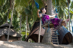 Sexy young woman sitting on the swing on the tropical beach, paradise island Bali, Indonesia. Sunny day, happy vacation. Sexy young woman sitting on the swing on Royalty Free Stock Image