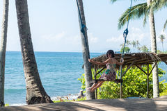 young woman sitting on the swing on the tropical beach, paradise island Bali, Indonesia. Sunny day, happy vacation Stock Photography
