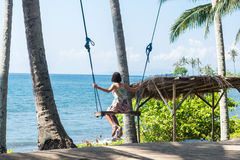 young woman sitting on the swing on the tropical beach, paradise island Bali, Indonesia. Sunny day, happy vacation Stock Photo