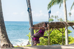 Sexy young woman sitting on the swing on the tropical beach, paradise island Bali, Indonesia. Sunny day, happy vacation Stock Photography