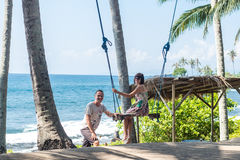 young woman sitting on the swing on the tropical beach, paradise island Bali, Indonesia. Sunny day, happy vacation Stock Photos