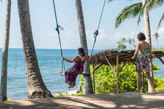 young woman sitting on the swing on the tropical beach, paradise island Bali, Indonesia. Sunny day, happy vacation Royalty Free Stock Photos