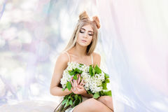 Sexy young woman sitting in tent with lilac flowers Royalty Free Stock Images