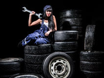 Sexy young woman sitting on wheels with a big wrench Royalty Free Stock Image