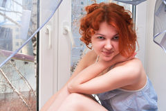 Sexy young woman sitting on the windowsill Royalty Free Stock Photos