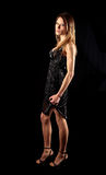 Sexy young woman in smart evening dress. Pretty young female standing in black evening dress and high heel shoes with black background Royalty Free Stock Photos