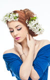 Sexy young woman with spring white flowers. Portrait of beautiful girl in studio with spring flowers in her hair. Sexy young woman in blue with bright white Stock Photography