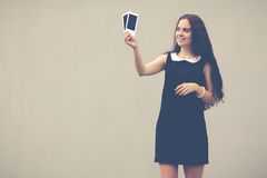 Sexy young woman standing near wall holding photos and smiling.Colorful hipster photo Stock Photo