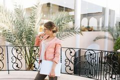 Sexy young woman, student with silver laptop standing on beautiful balcony, terrace in hotel, restaurant with palms in stock photos