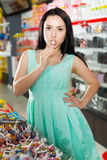 Sexy young woman suck lollipop at candy store Royalty Free Stock Images