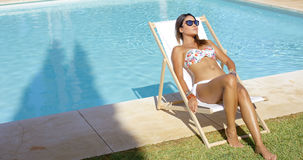 Sexy young woman sunbathing near a pool Royalty Free Stock Image