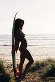 Sexy young woman with surfboard on beach Royalty Free Stock Images