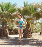 Sexy young woman in swimsuit on tropical island near palms Stock Images