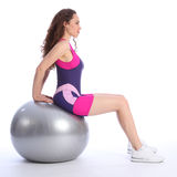 Young woman using ball for balance exercise. Concentrating on balance exercise, a beautiful young woman in sitting pose on fitness ball. She is wearing bright stock photo