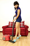 Woman in outfit uses vacuum cleaner Stock Images