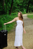 Sexy young woman waiting by road with suitcase Royalty Free Stock Photos