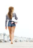 Sexy young woman walking barefoot. Portrait of a sexy young woman walking barefoot outdoors holding roller skates - from behind Royalty Free Stock Photography