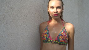 Young woman wearing bikini with wet hair and pink lipstick posing on a sunny day over white wall.  stock video