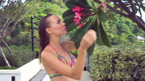 Sexy young woman wearing bikini with wet hair smelling tree flower at rooftop on a sunny day over blue sky and green trees. stock footage