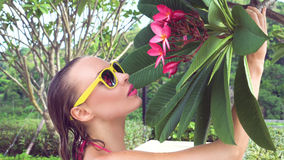 Sexy young woman wearing bikini with wet hair and tree flower on a sunny day. Closeup of sexy young woman wearing bikini and yellow sunglasses with wet hair Royalty Free Stock Photos
