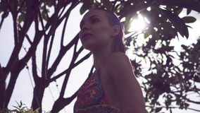 Young woman wearing bikini with wet hair walking on rooftop on a sunny day over blue sky and sun shining through green trees. Young woman wearing bikini with stock video