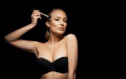 Sexy young woman wearing a bra applying foundation Royalty Free Stock Images