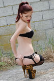 Sexy young woman wearing lingerie standing against cement tile wall Royalty Free Stock Image