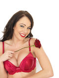 Sexy Young Woman Wearing Red Lingerie and Holding Red Roses Royalty Free Stock Image